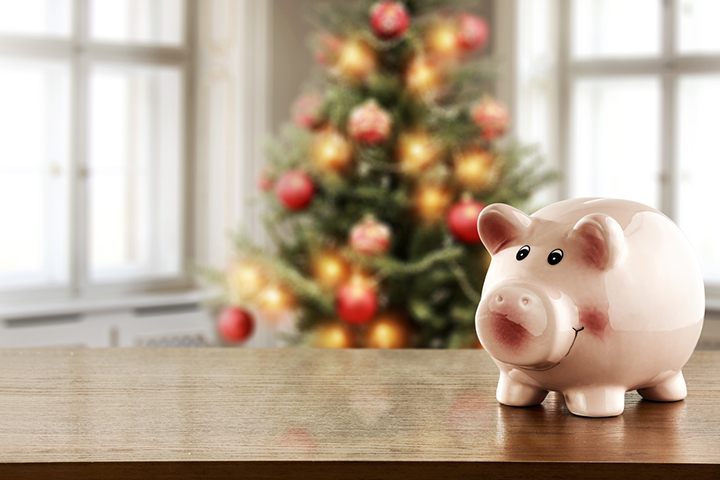 Piggy bank in front of a Christmas tree